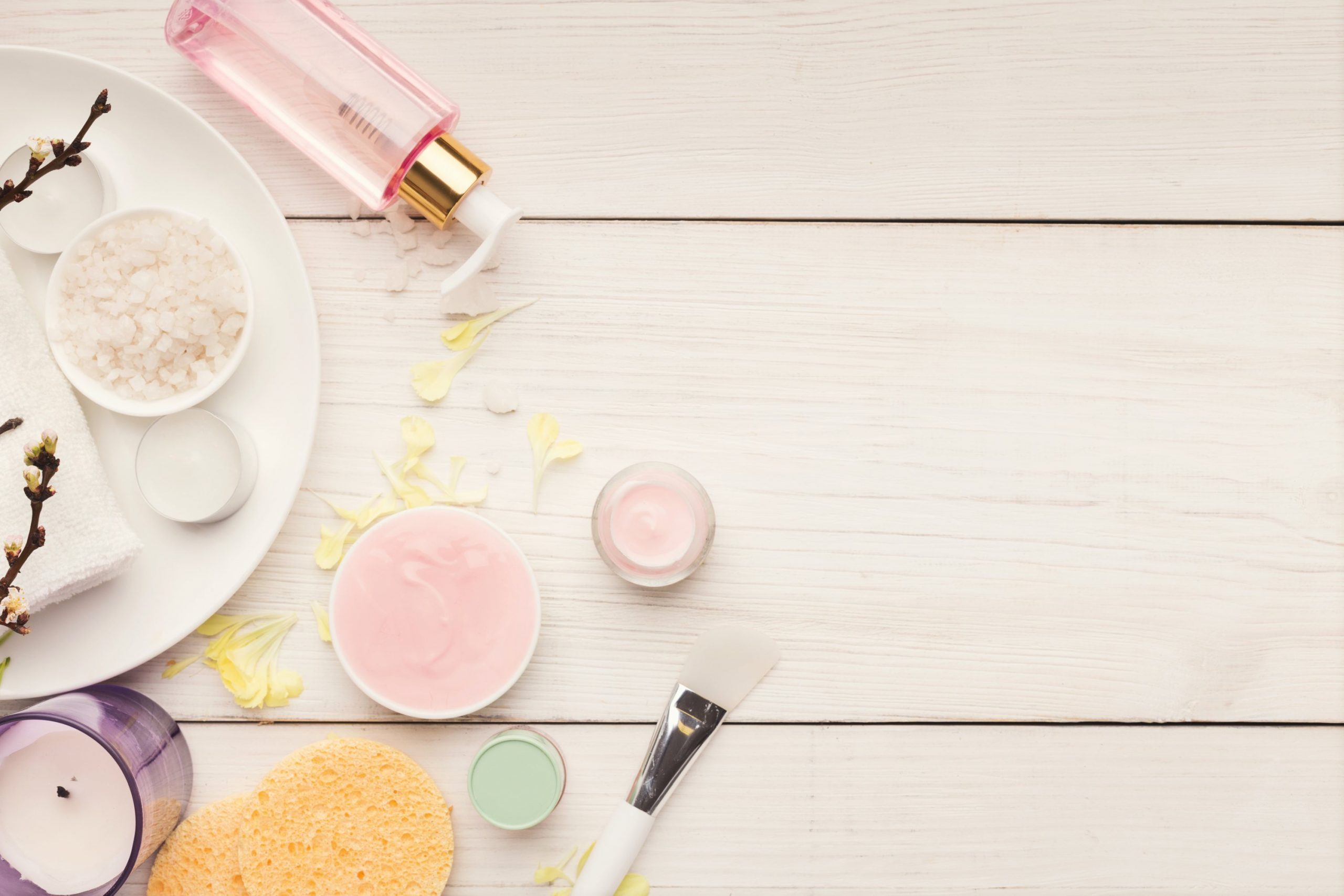 Various skincare products on white wood